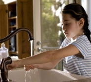 image of a child running tap water